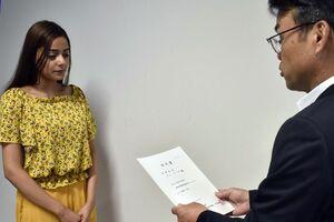 木内情報発信課長から認定書を交付される学生(左)=徳島市の四国大