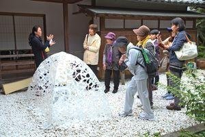 合田さん(左端)の展示解説を聞く参加者=三好市池田町の阿波池田たばこ資料館
