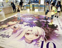改札付近の床一面に張られたアニメ作品のシールを眺める駅利用者ら=徳島駅