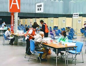 予診前に予診票の確認を受ける高齢者=5日午前9時10分ごろ、徳島市のアスティとくしま