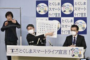 記者会見する仁井谷保健福祉部長(中央)=9日午後5時20分、県庁