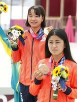 女子ストリートで優勝し、金メダルを手に笑顔を見せる西矢椛。手前は銅メダルの中山楓奈=有明アーバンスポーツパーク