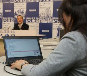 知事会見の発言を自動的に文字起こしした文章が表示されるパソコン画面を確認する県職員(右)=県庁