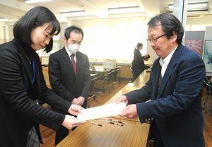 特色選抜の出願書類を提出する中学校の教員(右)=石井町の名西高校