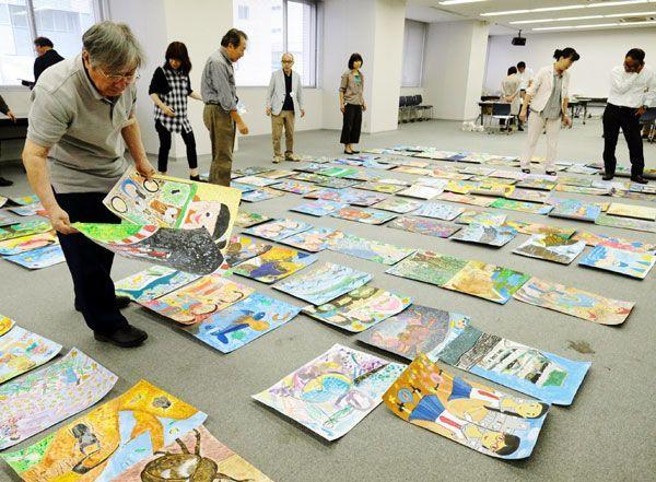 こども県展の応募作品を見る審査員ら=徳島新聞社