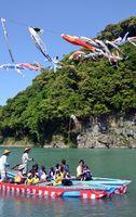 鯉まつりで、カンドリ舟に乗って楽しむ親子連れら=阿南市深瀬町の那賀川河川敷