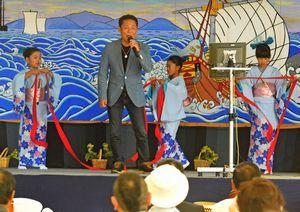 熱唱する石川さんと、踊りを披露する小学生=三好市西祖谷山村の祖谷源内の里小屋掛け舞台