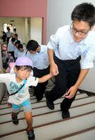 生徒に手を引かれて避難する園児=徳島市の徳島科学技術高校