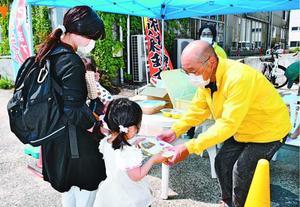 スタッフが調理したカレー弁当を受け取る親子=徳島市の万代中央埠頭