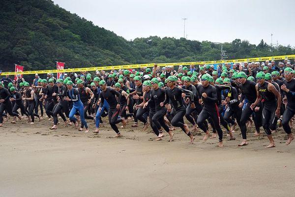 一斉に海に入るトライアスロン参加者=美波町日和佐浦の大浜海岸