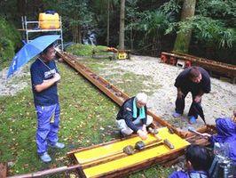 木枠に水を流し、水流と洪水の関係を調べる参加者=阿南市細野町谷尻