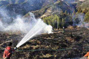 消火に当たる消防隊員ら=12日午後4時半ごろ、三好市池田町漆川