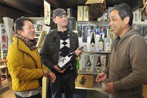 酒屋の店主(右)から話を聞くあべさん(左)とスウィーニーさん=三好市池田町マチ