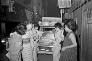 移動屋台からホットドッグを買い求める女性たち。当時はまだ珍しい食べ物だった=1966年、徳島市、本社所蔵写真