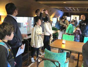 新型観光列車「四国まんなか千年ものがたり」に乗り込み、車内を見学する探検隊参加者=琴平駅