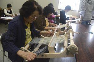 美馬市産の絹糸で織物を楽しむ参加者=同市の旧脇町庁舎