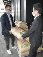 宮本部長(右)に米を手渡す北野さん=吉野川市鴨島町の市民プラザ