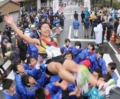 4連覇を果たし、仲間に胴上げされる鳴門のアンカー元木選手=6日、徳島市幸町の新聞放送会館別館前