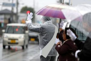降りしきる雨の中、ドライバーに手を振って支持を訴える候補者=午前10時、北島町中村