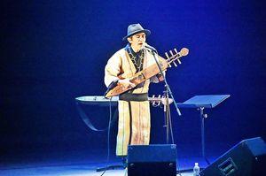 トンコリを演奏しながら歌うOKIさん=阿南市富岡町の市文化会館夢ホール