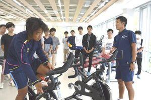教員(右端)からトレーニング用自転車の使い方の説明を受ける学生=徳島市の徳島文理大