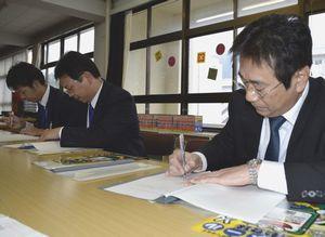 協定書に署名する徳島新聞専売所長=徳島市の加茂名中