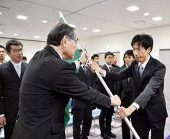 岩浅市長から市旗を受け取る阿南市チームの森監督(右端)=阿南市富岡町の市商工業振興センター