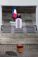 フランス・パリで催されたテロ犠牲者の国家追悼式で、ひつぎを前に演説するマクロン大統領=21日(AP=共同)