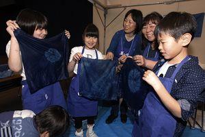 藍色に染めたハンカチを見せ合う児童=徳島市のアスティとくしま
