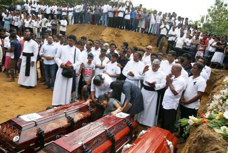 23日、スリランカ西部ネゴンボで営まれた連続爆破テロの犠牲者の葬儀。ひつぎのそばで女性が泣き崩れていた(ロイター=共同)