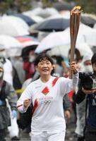 聖火のトーチを掲げて走る高畑響子さん=17日午前、香川県丸亀市