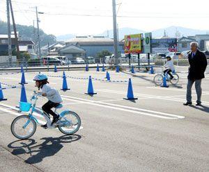 駐車場の一角を利用して自転車の練習に取り組む児童ら=鳴門市撫養町の鳴門競艇場