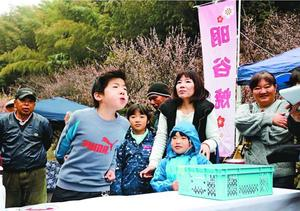 梅干しの種を飛ばす参加者=阿南市の「明谷梅林 令和園」