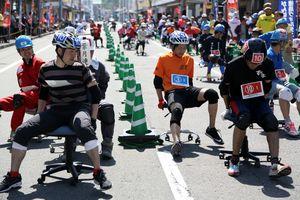 横滑りしながらコーナーを駆け抜ける参加者=鳴門市撫養町の大道商店街