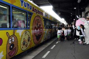 園児らに見送られて出発する新しいアンパンマンカー=JR徳島駅