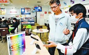 来店者に5G対応のスマホをPRするスタッフ(右)=徳島市中吉野町のドコモショップ田宮街道店