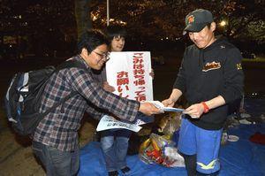花見客(右)にごみの持ち帰りを呼び掛ける会員ら=徳島中央公園