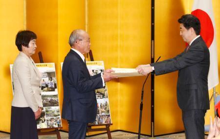 「ふるさとづくり大賞」を受賞し、安倍首相(右)から表彰状を受け取る豊重哲郎さん=13日午後、首相官邸