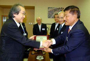 植田社長(左)に盾を手渡し、握手を交わすビシュヌ会長=徳島市の徳島新聞社