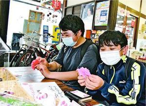 花紙を1枚ずつ広げ、カーネーションを作る子ども=勝浦町生名の道の駅「ひなの里かつうら」