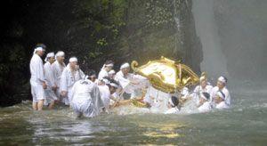 滝つぼでみこしを沈める信者=海陽町平井の轟の滝