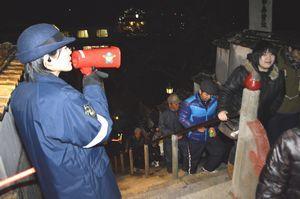 足元に注意して石段を登るよう呼び掛けるTKポリス(左)=1日午前0時すぎ、美波町の薬王寺
