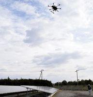 上空から太陽光発電パネルを点検するための画像を撮影するドローン=小松島市和田島町松田新田の和田島太陽光発電所