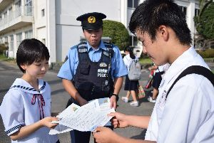 非行防止を訴えるチラシを手渡す生徒会役員(左)=徳島市の富田中