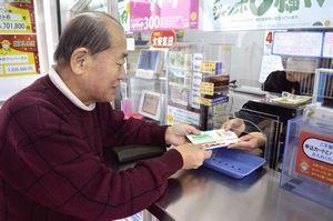 高額当せんを願ってグリーンジャンボ宝くじを買う客=徳島市のみずほ銀行徳島支店の売り場
