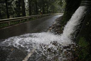 擁壁の排水口から勢いよく県道に流れ出す雨水=3日午前11時ごろ、三好市山城町上名