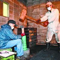 火薬を詰め、吹筒花火を完成させる住民=美波町赤松の作業場