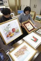 即売展に向けて作品を整理する社会文化事業団職員=徳島新聞社