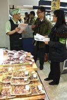 従業員(左)に食中毒対策の徹底を呼び掛ける食品衛生監視員=徳島市のそごう徳島店