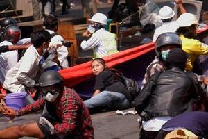 3日、ミャンマー中部マンダレーで銃撃される前に地面に伏せるチャル・シンさん(中央)(ロイター=共同)
